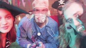 Grupo de gente joven que baila y que bebe en un partido de Halloween almacen de video