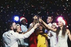 Grupo de gente joven que celebra Año Nuevo con champán en el club de noche Imagen de archivo