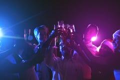 Grupo de gente joven que celebra Año Nuevo con champán en el club de noche Imagen de archivo libre de regalías