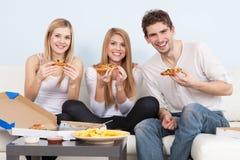 Grupo de gente joven que come la pizza en casa Foto de archivo
