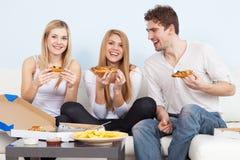 Grupo de gente joven que come la pizza en casa foto de archivo libre de regalías