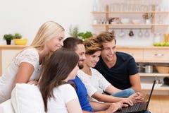 Grupo de gente joven que comparte un ordenador portátil Fotos de archivo