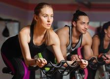 Grupo de gente joven que completa un ciclo en clase en gimnasio Fotos de archivo