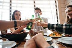 Grupo de gente joven que dice alegrías y que come comidas sanas Fotos de archivo