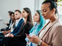Grupo de gente joven que espera una entrevista del bastidor o de trabajo fotografía de archivo libre de regalías