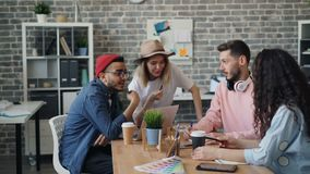 Grupo de gente joven que habla y que ríe discutiendo ideas del negocio en oficina metrajes