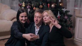 Grupo de gente joven que hace Selfie cerca del árbol de navidad Concepto de la celebración de la Feliz Año Nuevo almacen de metraje de vídeo