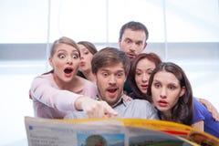 Grupo de gente joven que lee el periódico. Fotografía de archivo