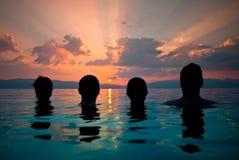 Grupo de gente joven que mira la puesta del sol Imagen de archivo libre de regalías