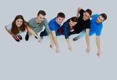 Grupo de gente joven que señala en algo Imágenes de archivo libres de regalías