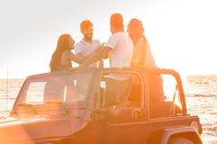 Grupo de gente joven que se divierte en coche convertible en la playa en la puesta del sol Foto de archivo