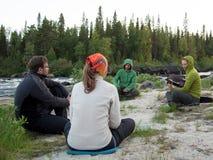 Grupo de gente joven que se sienta en el banco del río Fotos de archivo