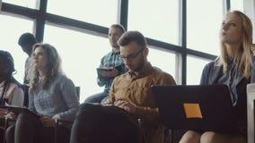 Grupo de gente joven que se sienta en oficina del desván y que escucha el seminario Los estudiantes con el ordenador portátil y l almacen de video