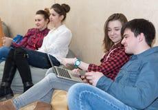 Grupo de gente joven que se sienta en sofá y la charla imagenes de archivo