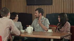 Grupo de gente joven que se sienta en un café, hablar y el goce metrajes