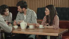 Grupo de gente joven que se sienta en un té del café, el hablar y de la consumición Foto de archivo libre de regalías