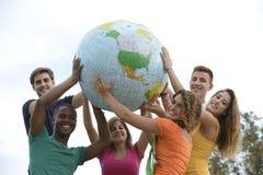 Grupo de gente joven que sostiene una tierra del globo Imagenes de archivo