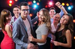 Grupo de gente joven que tiene baile de la diversión en el partido foto de archivo