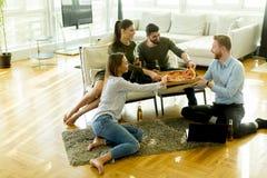 Grupo de gente joven que tiene partido de la pizza Imagen de archivo libre de regalías