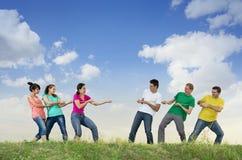 Grupo de gente joven que tira de una cuerda Imagen de archivo libre de regalías