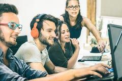 Grupo de gente joven que trabaja con el ordenador en oficina de lanzamiento imágenes de archivo libres de regalías