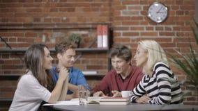 Grupo de gente joven que trabaja en proyecto en el apartamento moderno del desván metrajes