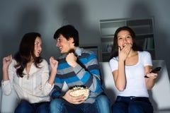 Grupo de gente joven que ve la TV en el sofá Foto de archivo libre de regalías