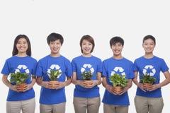 Grupo de gente joven sonriente en fila que lleva reciclando las camisetas del símbolo y sosteniendo las plantas en conserva, tiro  Fotos de archivo libres de regalías