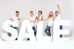 Grupo de gente joven sonriente que presenta con las letras de la venta Imagen de archivo libre de regalías