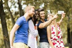 Grupo de gente joven y de pares que toman selfies en naturaleza Foto de archivo