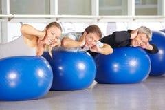 Grupo de gente mayor en las bolas del gimnasio que hacen el entrenamiento trasero Imagenes de archivo