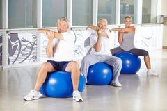 Grupo de gente mayor que estira en gimnasio Fotografía de archivo