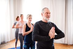 Grupo de gente mayor que hace ejercicio de la yoga en club del centro de la comunidad fotos de archivo