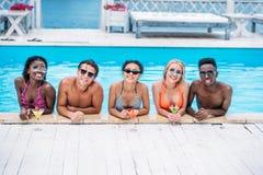 Grupo de gente multiétnica feliz joven con los cócteles en la natación foto de archivo libre de regalías