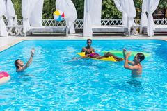 Grupo de gente multiétnica feliz joven que se divierte junto en la natación foto de archivo libre de regalías