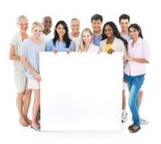 Grupo de gente multiétnica que lleva a cabo el cartel en blanco Imagen de archivo libre de regalías
