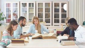 Grupo de gente multirracial que estudia con los libros en biblioteca de universidad almacen de video