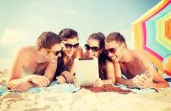 Grupo de gente sonriente con PC de la tableta en la playa Fotos de archivo libres de regalías