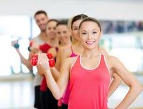 Grupo de gente sonriente con pesas de gimnasia en el gimnasio Imagen de archivo libre de regalías