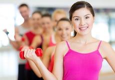 Grupo de gente sonriente con pesas de gimnasia en el gimnasio Imagenes de archivo