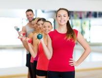 Grupo de gente sonriente con pesas de gimnasia en el gimnasio Fotos de archivo