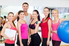 Grupo de gente sonriente en el gimnasio Imagen de archivo libre de regalías