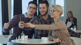 Grupo de gente sonriente feliz que toma un autorretrato en un café mientras que teniendo una rotura almacen de video