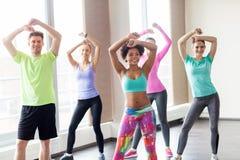 Grupo de gente sonriente que baila en gimnasio o estudio Foto de archivo libre de regalías