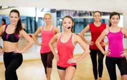 Grupo de gente sonriente que ejercita en el gimnasio Fotografía de archivo libre de regalías
