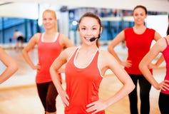 Grupo de gente sonriente que ejercita en el gimnasio Imagen de archivo libre de regalías