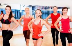 Grupo de gente sonriente que ejercita en el gimnasio Fotografía de archivo