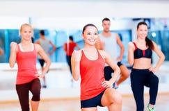 Grupo de gente sonriente que ejercita en el gimnasio Fotos de archivo libres de regalías