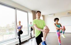 Grupo de gente sonriente que ejercita en gimnasio Fotografía de archivo libre de regalías