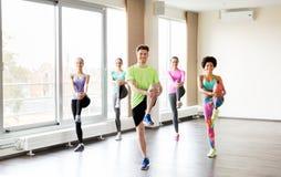 Grupo de gente sonriente que ejercita en gimnasio Foto de archivo